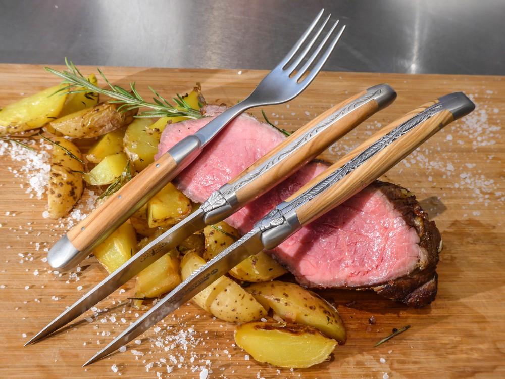 Messer Wien Steakmesser und Gabel mit Olivenholzgriff mit einer Klinge aus Sandvikstahl. Daneben ein Taschenmesser in der gleichen Ausführung. forge de laguiole steakbesteck klappmesser olive sandvik stahl